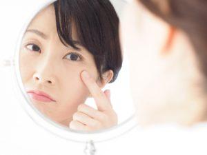 鏡を見て目じりを気にしている女性