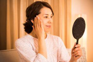 頬に手をあてて鏡を見る40代女性