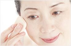 目元を化粧する50代女性