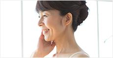 頬を触る笑顔の40代女性