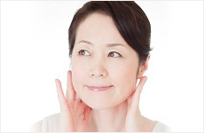 顎に手を当てている40代女性