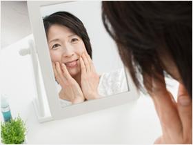 鏡を見て頬を触っている50代の女性